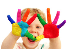 Stock image of a boy with painted hands in-front of his face