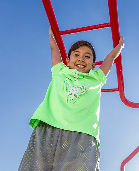 Stock image of a young boy handing from monkey bars